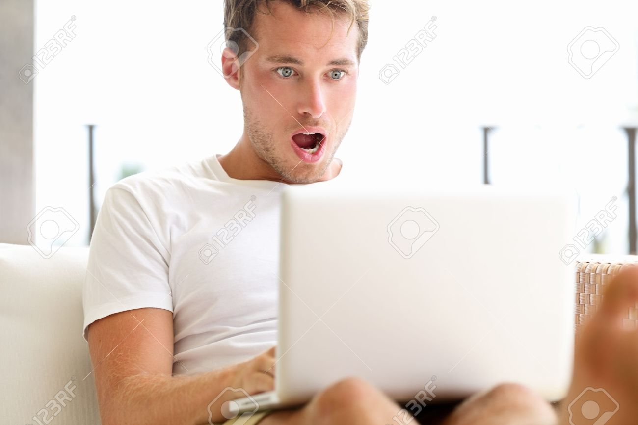 Shocked surprised man looking at laptop computer surprised and amazed with open mouth and big eyes. Funny young male model sitting outside on sofa. Stock Photo - 18730937