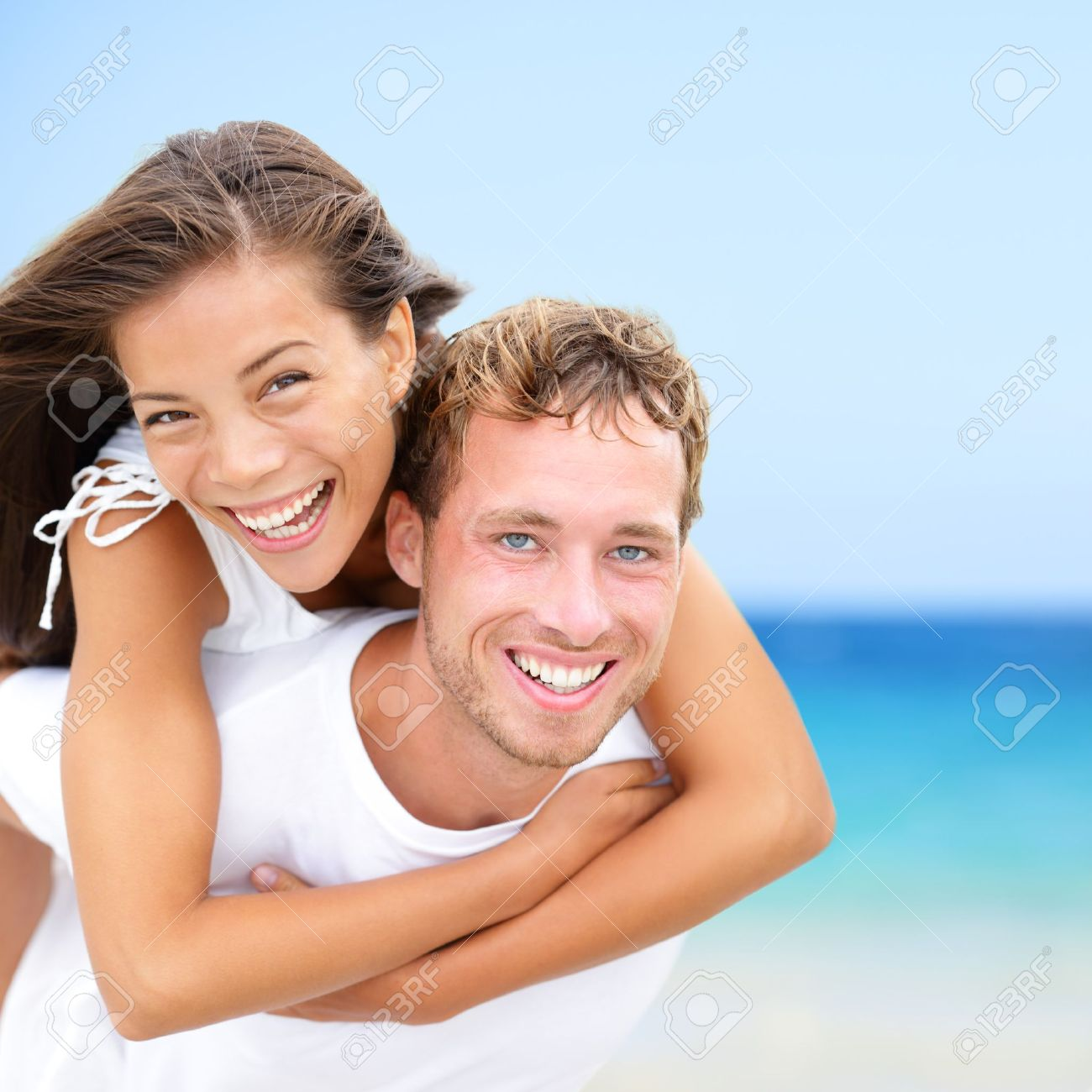 Happy couple on beach fun summer vacation  Multiracial Young newlywed couple piggybacking smiling joyful elated in happiness concept on tropical beach with blue water, sky  Asian woman, Caucasian man Stock Photo - 18969026