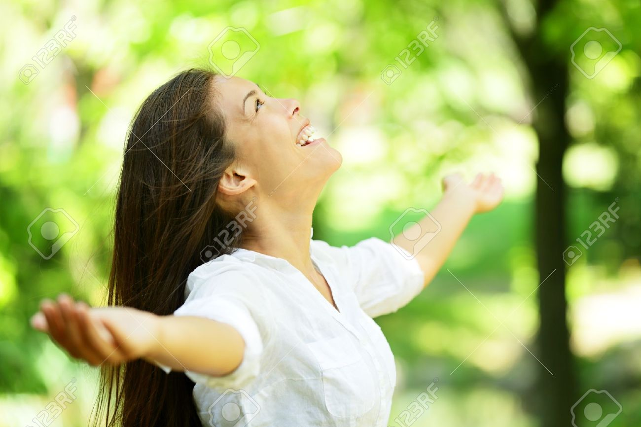 Attractive young woman rejoicing in a spring or summer garden standing sideways with her arms outstretched and her head raised to the heavens enjoying the freshness and beauty of nature Stock Photo - 19203333