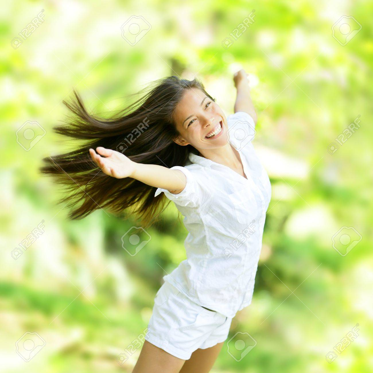 Rejoicing happy woman in flying motion smiling full of joy and vitality in summer or spring forest. Eurasian female model. - 19203324