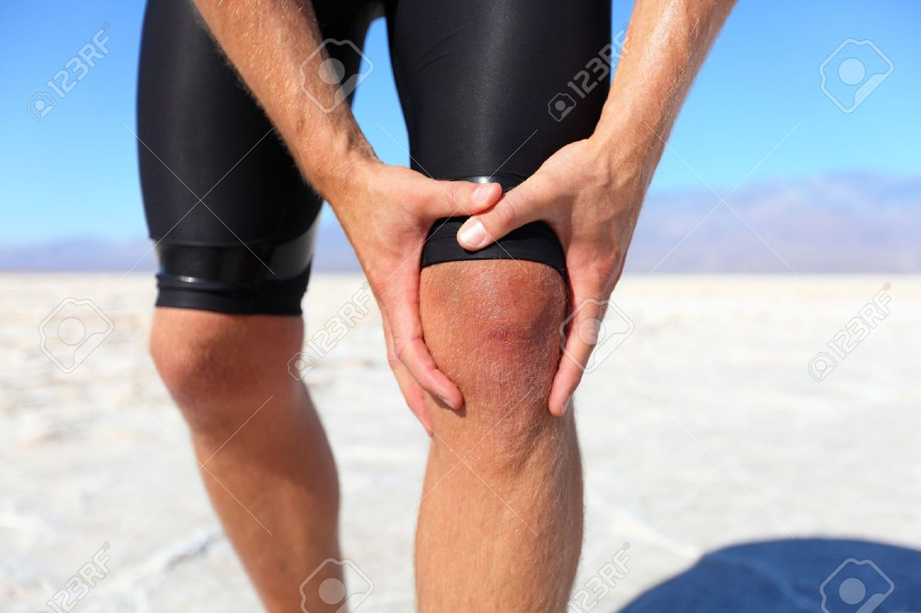 Injuries - sports running knee injury on man. Male runner with pain, maybe from sprain knee. Close up of legs, muscle and knee outdoors. Stock Photo - 19359128