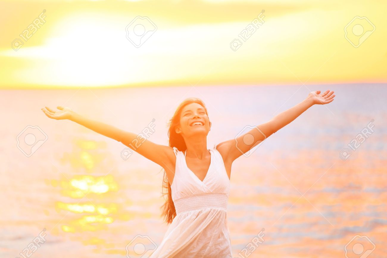 Freedom woman happy and free open arms on beach at sunny sunset. Beautiful joyful elated woman looking up smiling by the ocean during summer holidays vacation. Pretty multiracial Asian Caucasian girl. - 19387053