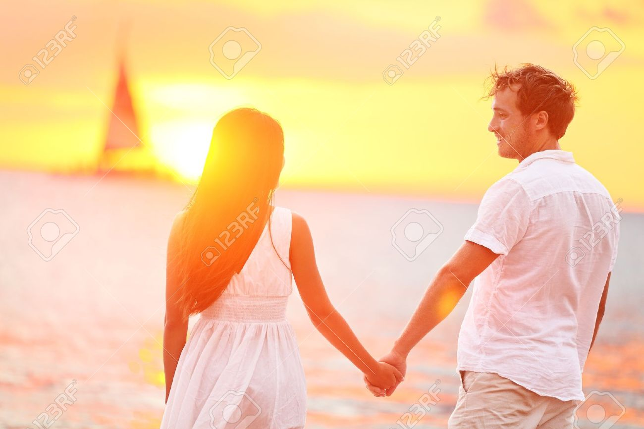 Couple in love happy at romantic beach sunset. Young interracial couple holding hands having romance and fun outside walking on beach during summer holidays vacation travel together. Enjoying sunshine Stock Photo - 19387046