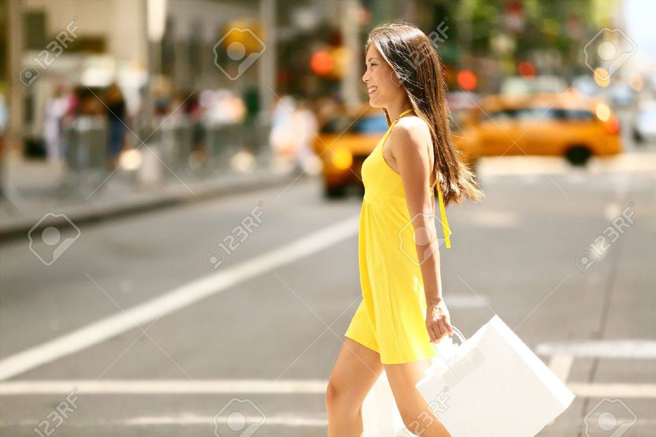 Shopping woman walking outside in New York City holding shopping bags. Shopper smiling happy crossing the street outdoors while on travel on Manhattan, United States. Beautiful model in summer dress. - 19387047