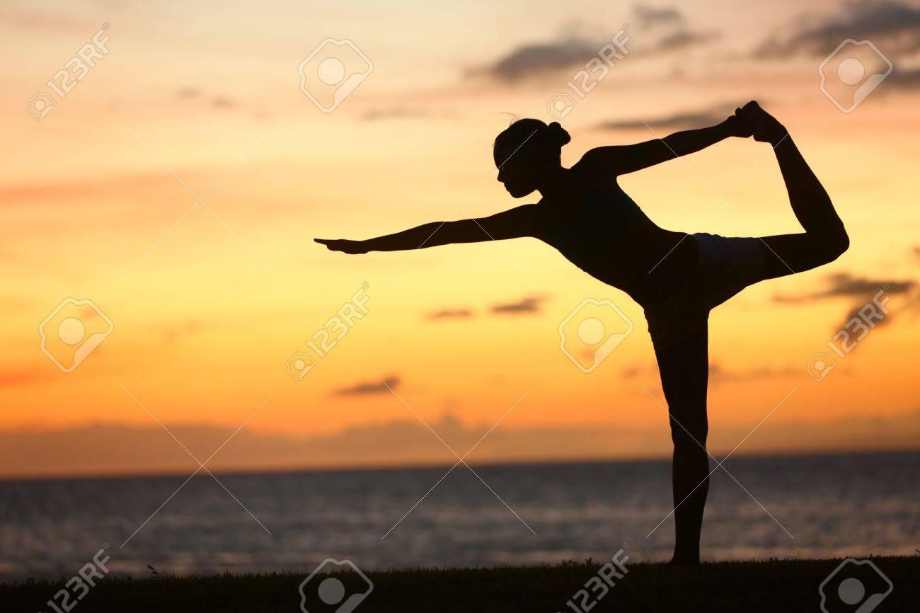 Yoga woman in serene sunset at beach doing king dancer pose - 19502390