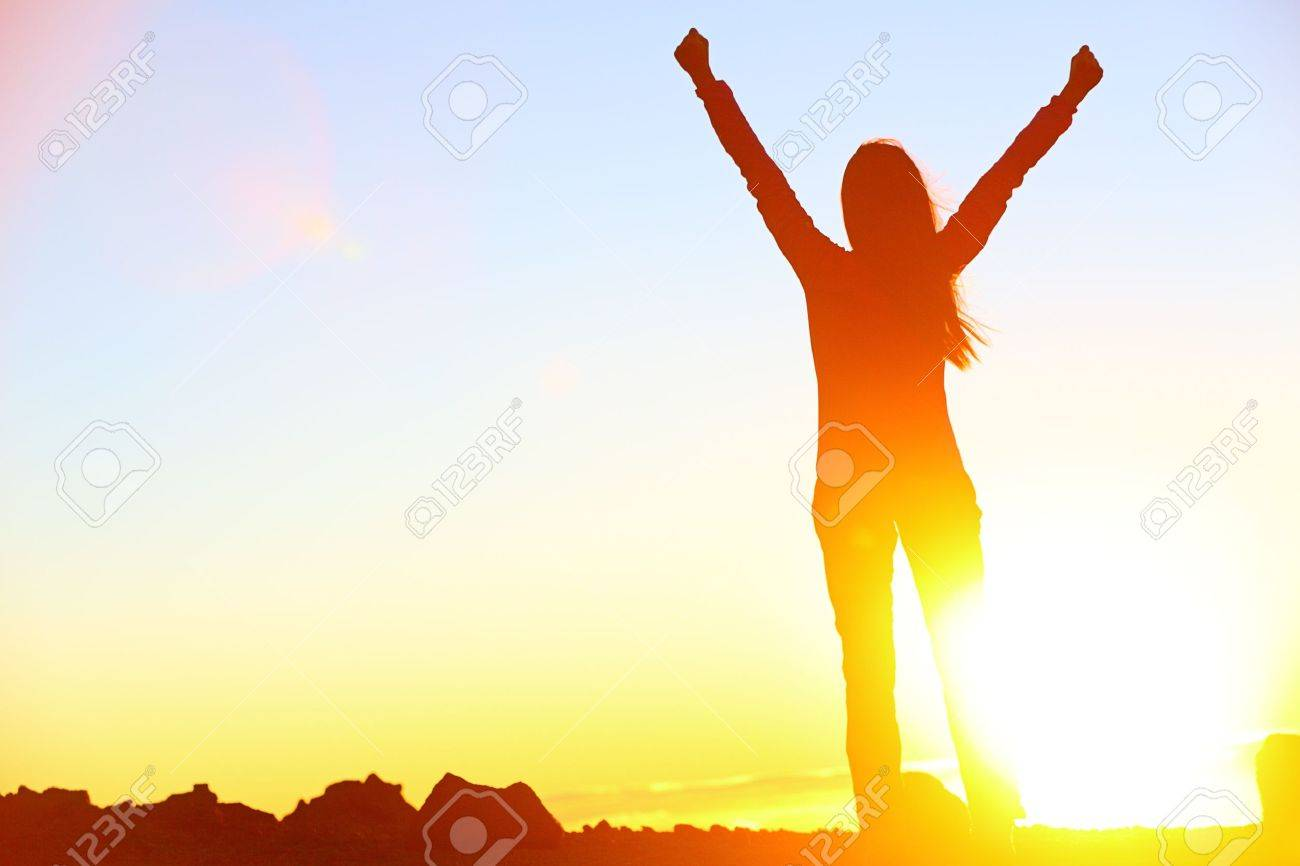 Happy celebrating winning success woman at sunset or sunrise standing elated with arms raised up above her head in celebration of having reached mountain top summit goal during hiking travel trek - 19557902