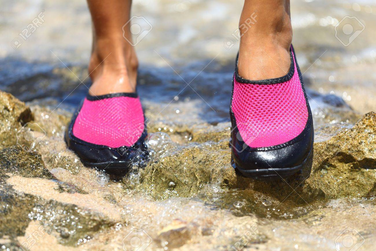 Closeup detail of the feet of a woman wearing bright pink neoprene water shoes standing on rocks Stock Photo - 19983204