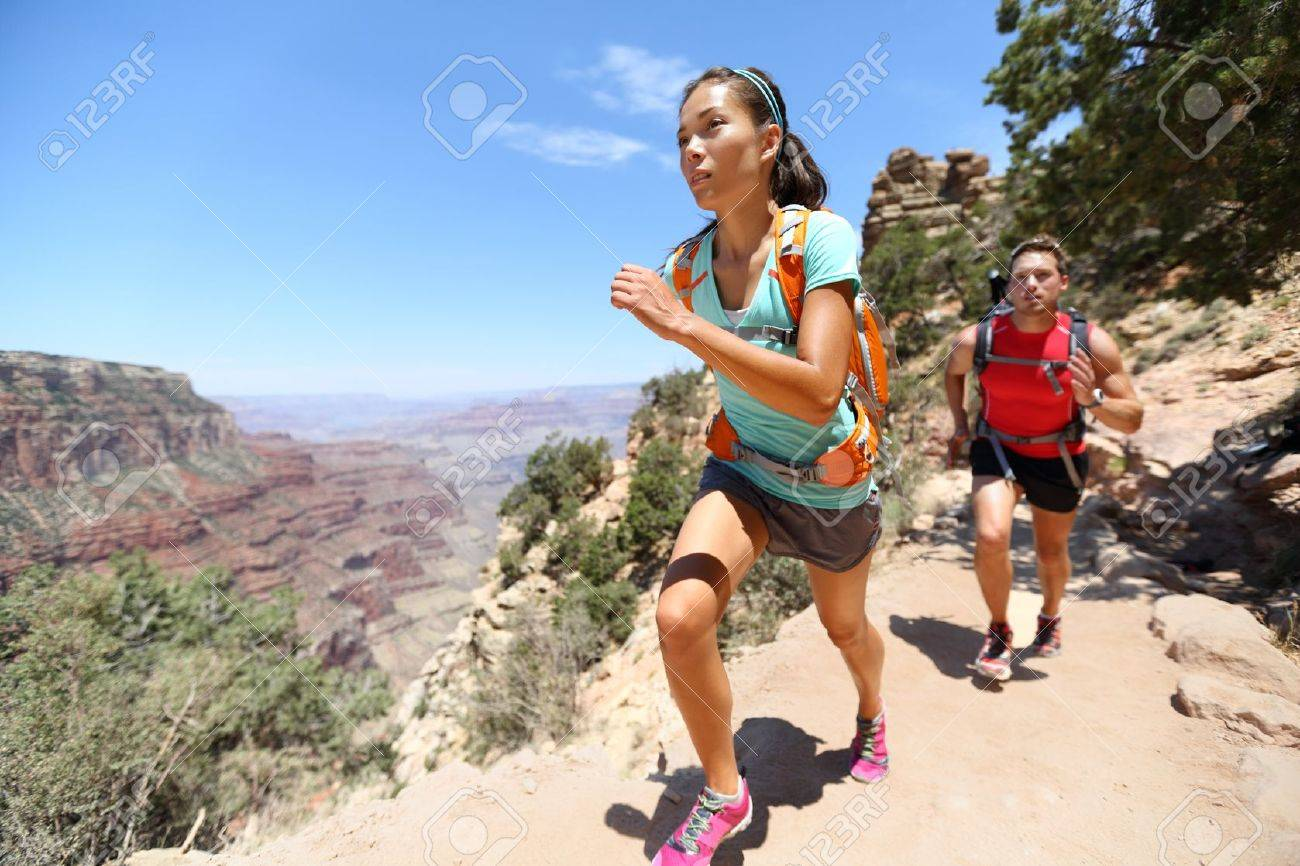 Trail running cross-country runners in race on path in Grand Canyon, USA. Fit athletes jogging and training together in beautiful nature landscape. Asian fitness woman, Caucasian fit model. - 20019962