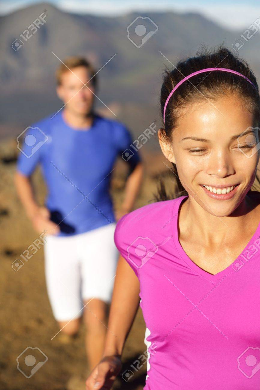 Happy healthy lifestyle running people. Woman runner smiling happy during cross country run in beautiful nature. Female fitness sport jogger and man training trail running together outside. Stock Photo - 20617439