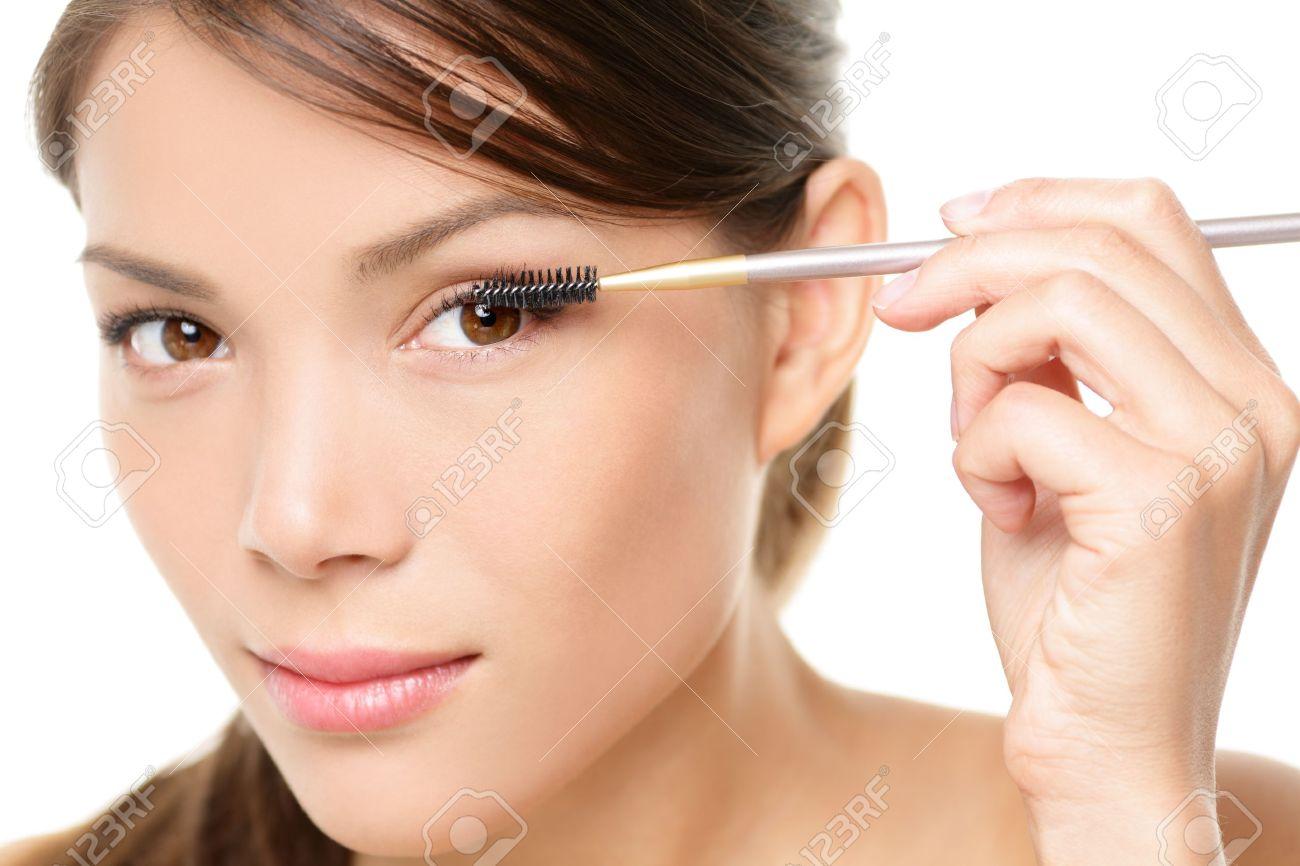 Mascara woman putting makeup on eyes. Asian female model face closeup with eye brush on eyelashes. Stock Photo - 21144527