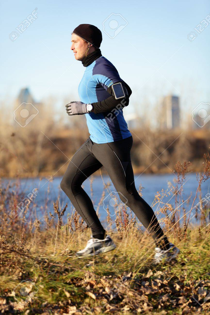 Running man jogging in autumn listening to music on smart phone. Runner training in warm outfit on cold day. Fit male fitness athlete model training outdoor in fall. Full body length of jogger. Stock Photo - 21172696