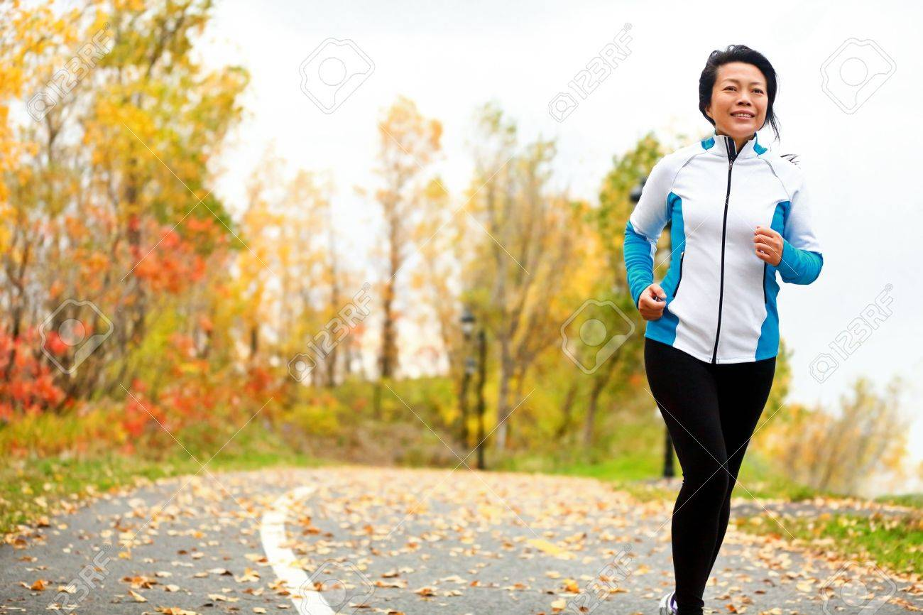 mature asian woman running active in her 50s. middle aged female