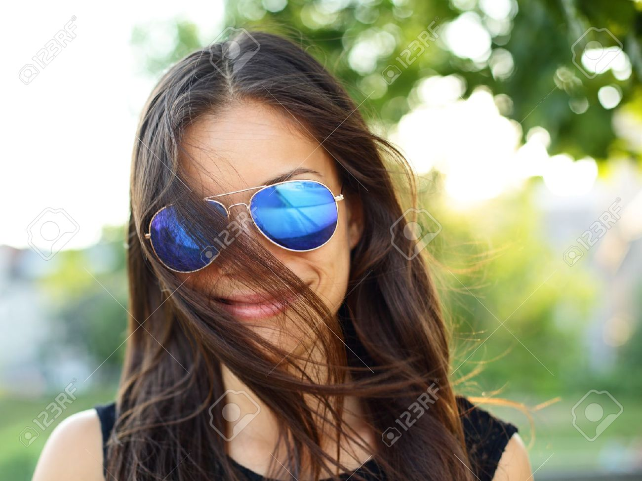 Sunglasses woman funky portrait outdoor with hair flying. Young girl wearing colored sunglasses outside looking at camera smiling happy, Young cool modern multiracial female model girl in her 20s, Stock Photo - 21232784