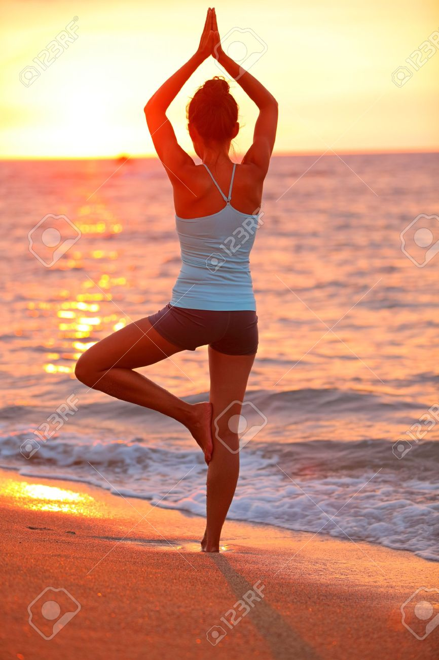 Yoga meditation woman meditating at beach sunset relaxing in yoga posture, tree pose, vrksasana. Relaxed serene Asian woman enjoying evening sun light and sunshine. From Big Island, Hawaii, USA. Stock Photo - 21379854