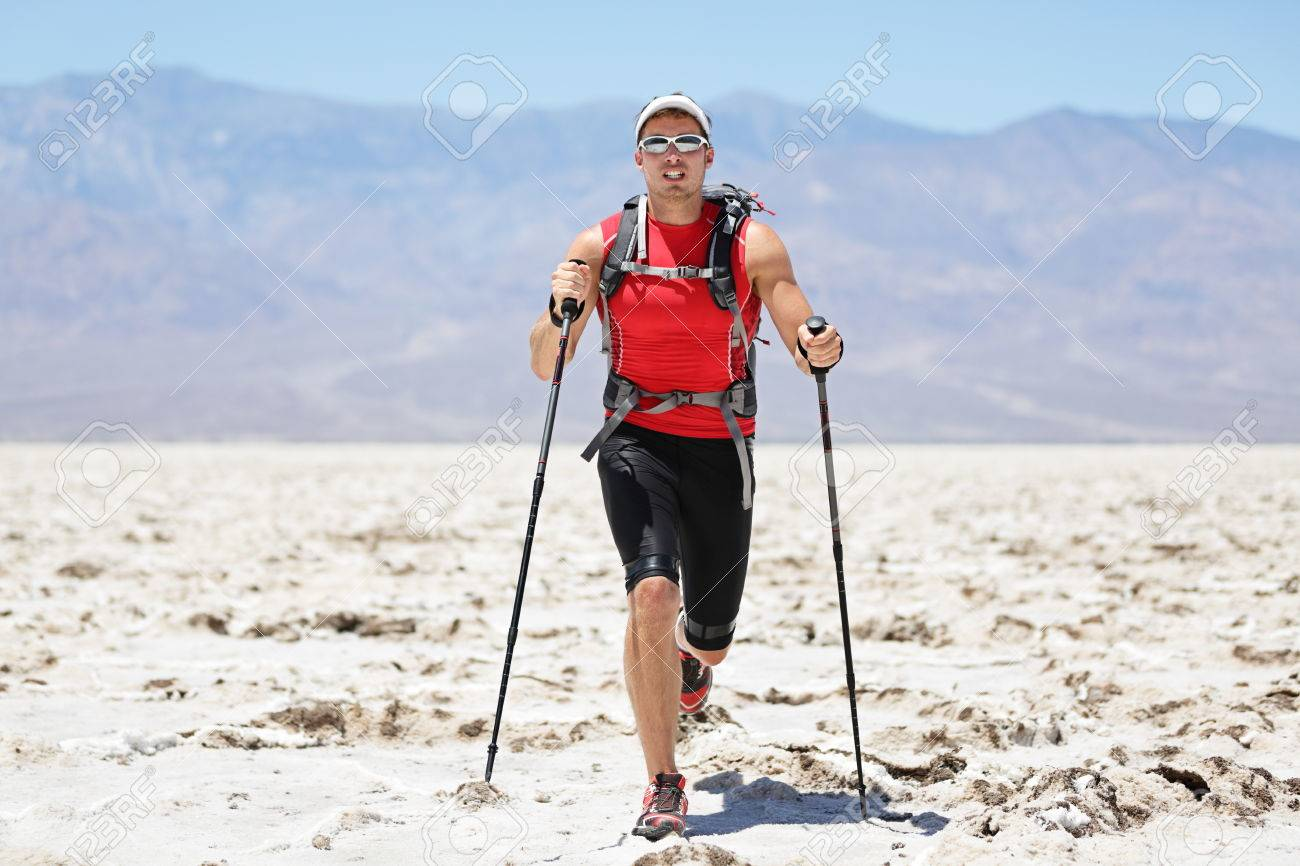 Ultra running man - trail runner in extreme race training for marathon. Fit male athlete running with trekking hiking poles in Death Valley, USA. - 23265323