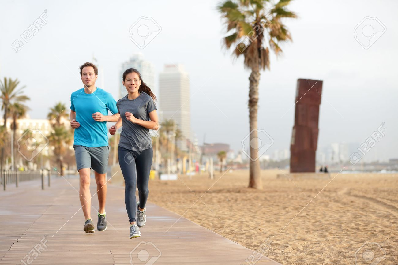 Running couple jogging on Barcelona Beach, Barceloneta. Healthy lifestyle people runners training outside on boardwalk. Multiracial couple, Asian woman, Caucasian fitness man working out, Spain. - 26735503