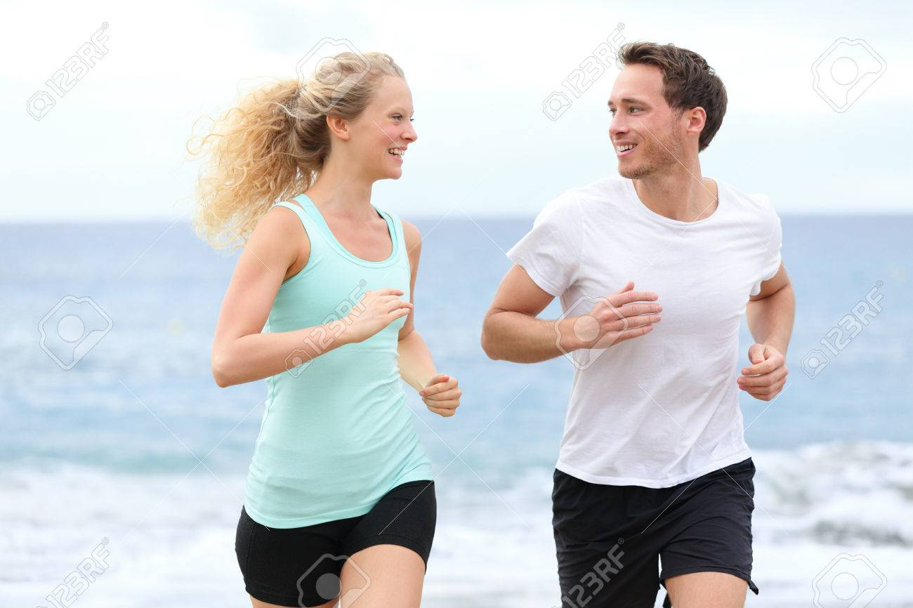 2cad51e9fb780 Running couple jogging exercising on beach talking and training as part of  healthy lifestyle Two fit