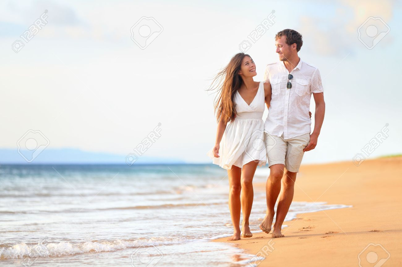 Beach couple walking on romantic travel honeymoon vacation summer holidays romance. Young happy lovers, Asian woman and Caucasian man holding hands embracing outdoors. Stock Photo - 27539928