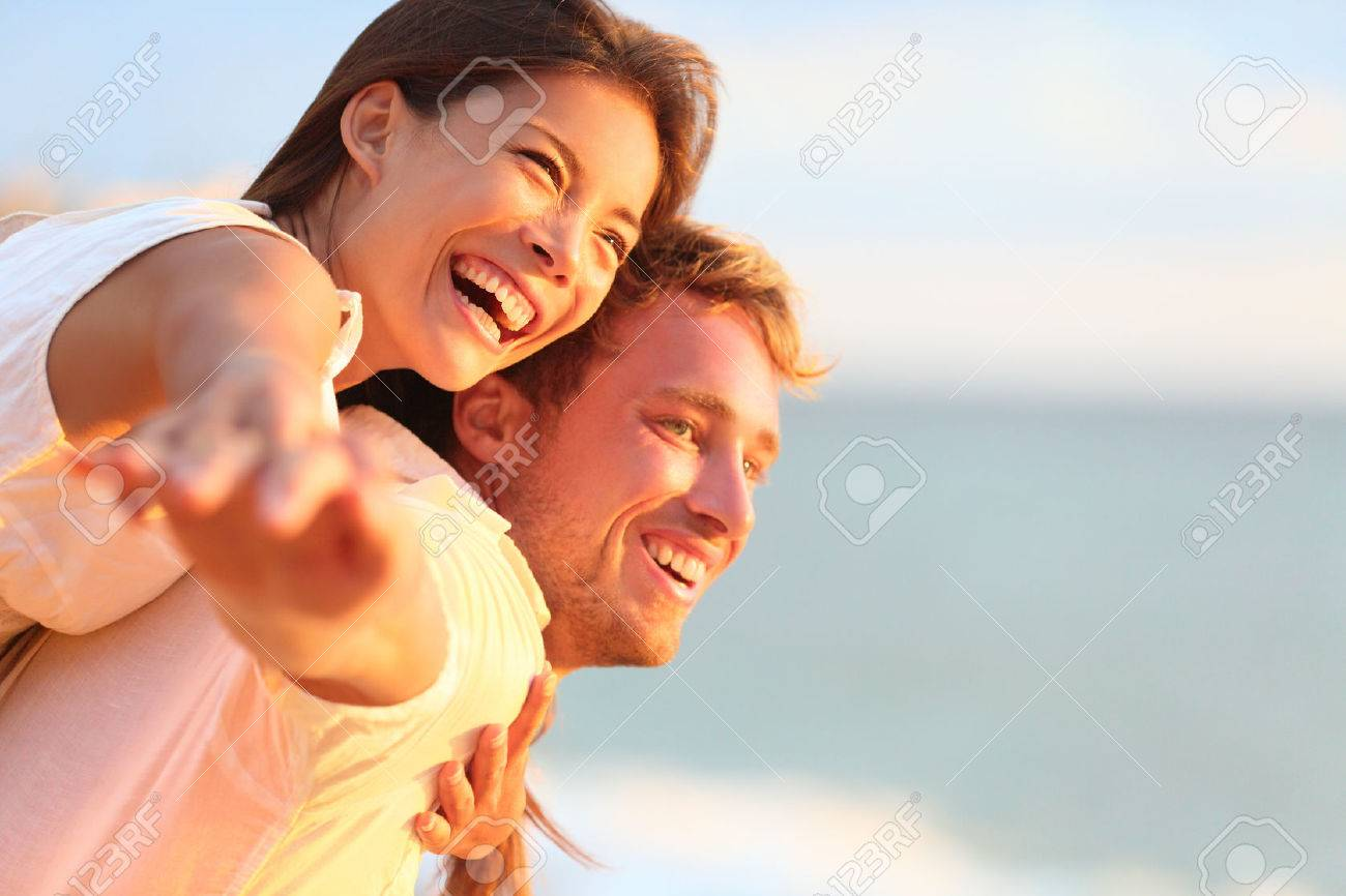 Beach couple laughing in love romance on travel honeymoon vacation summer holidays romance. Young happy people, Asian woman and Caucasian man embracing outdoors on tropical beach in casual wear. Stock Photo - 28001356