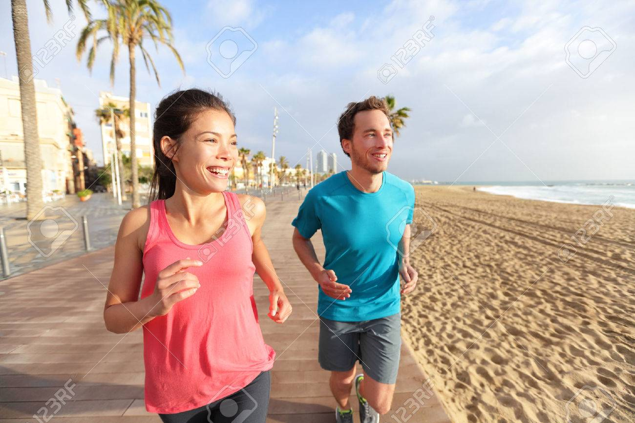 109266c110151 Running man and woman couple jogging on Barcelona Beach, Barceloneta.  Healthy lifestyle people runners
