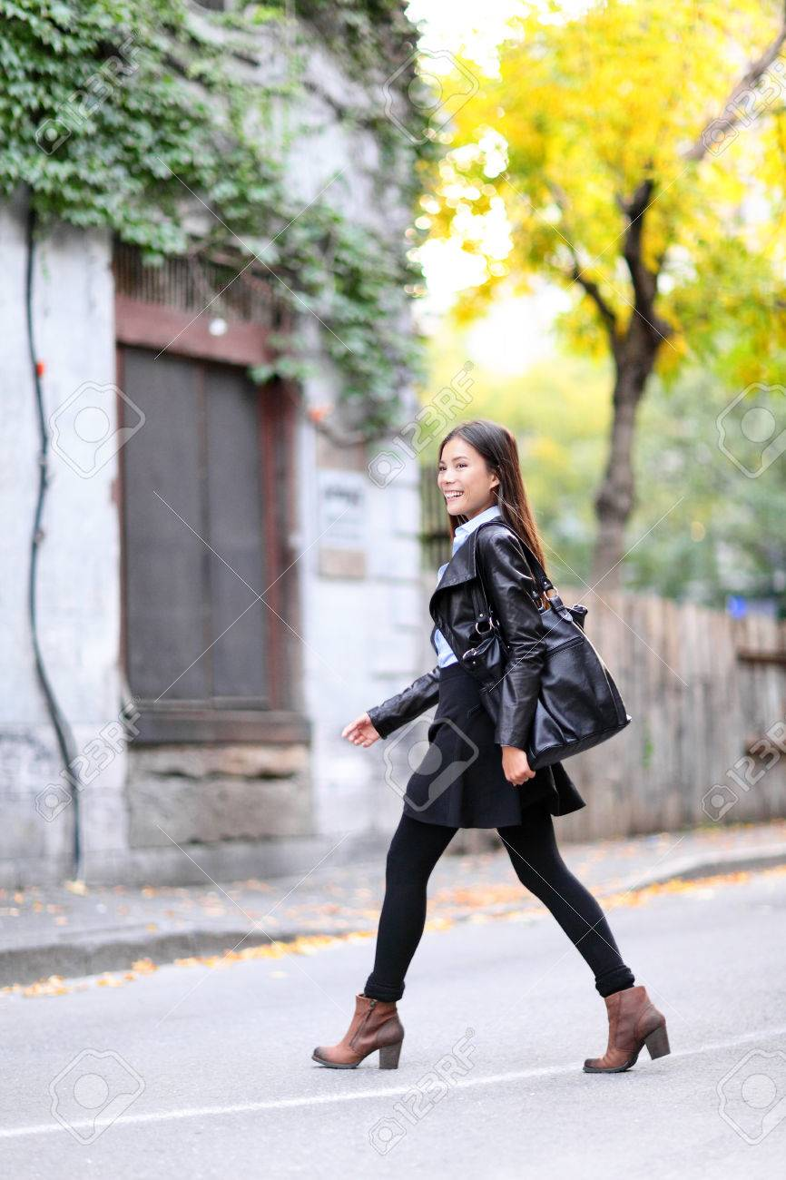 Urban young woman walking in leather jacket in city crossing streets in full length in autumn fall. Trendy modern female living city lifestyle. Multiracial Asian Caucasian model. Stock Photo - 28635953