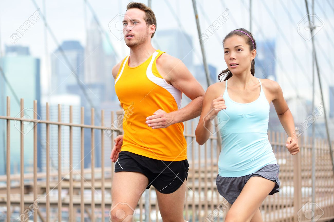 Running couple jogging training for New York marathon. Runners on run outside. Asian woman and Caucasian man runner and fitness sport models jogging on Brooklyn Bridge, New York City, USA. Stock Photo - 29880226