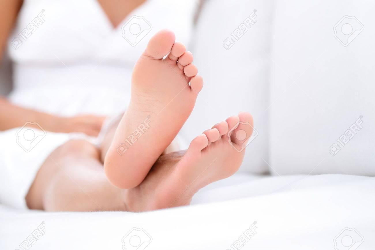woman feet closeup - barefoot woman relaxing in sofa. close up