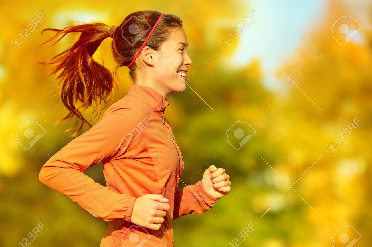 Woman runner running in fall autumn forest. Female fitness girl jogging on path in amazing fall foliage landscape nature outside. - 32442086