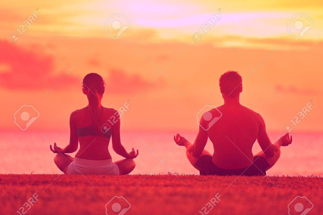 Meditation yoga couple meditating at serene beach sunset. Girl and man relaxing in lotus pose in calm zen moment in the ocean during yoga holiday class at resort retreat. - 37149271
