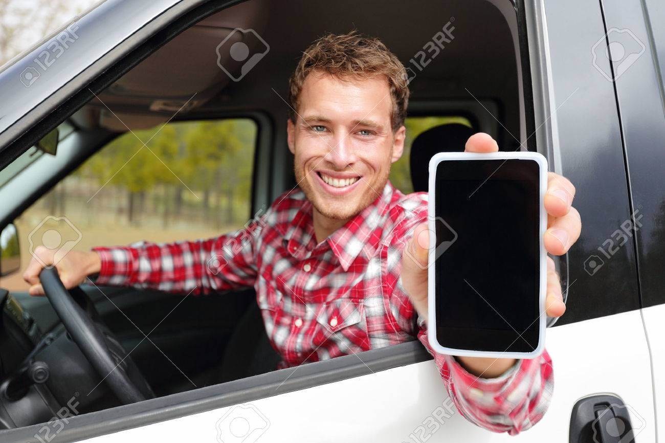 Smartphone man driving car showing app on screen display smiling