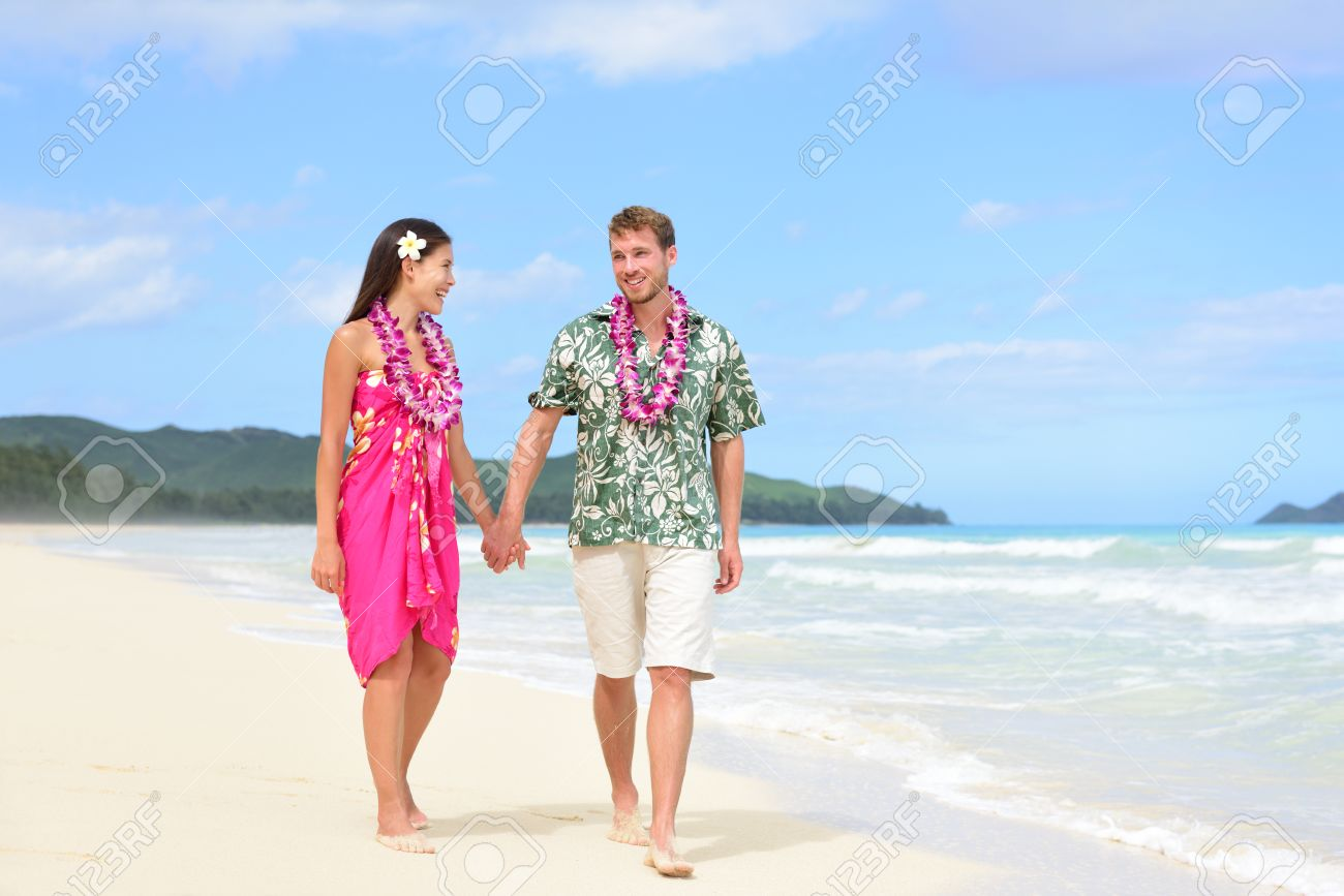 d9019b85f98 Happy couple on Hawaii vacation walking on beach with Hawaiian leis and  Aloha clothing. Caucasian