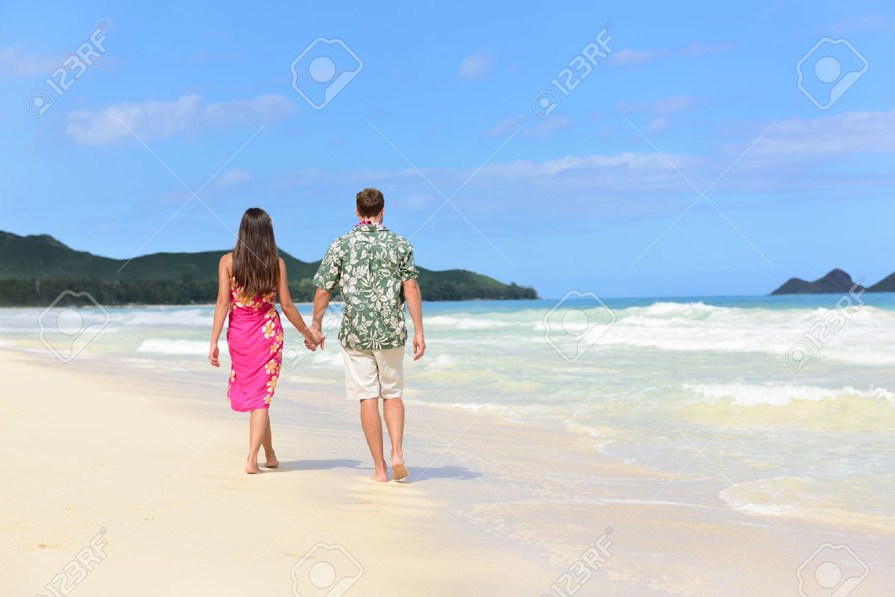 Hawaii Honeymoon Couple Of Newlyweds Walking On Tropical Beach In Hawaiian Apparel Pink Sarong Dress