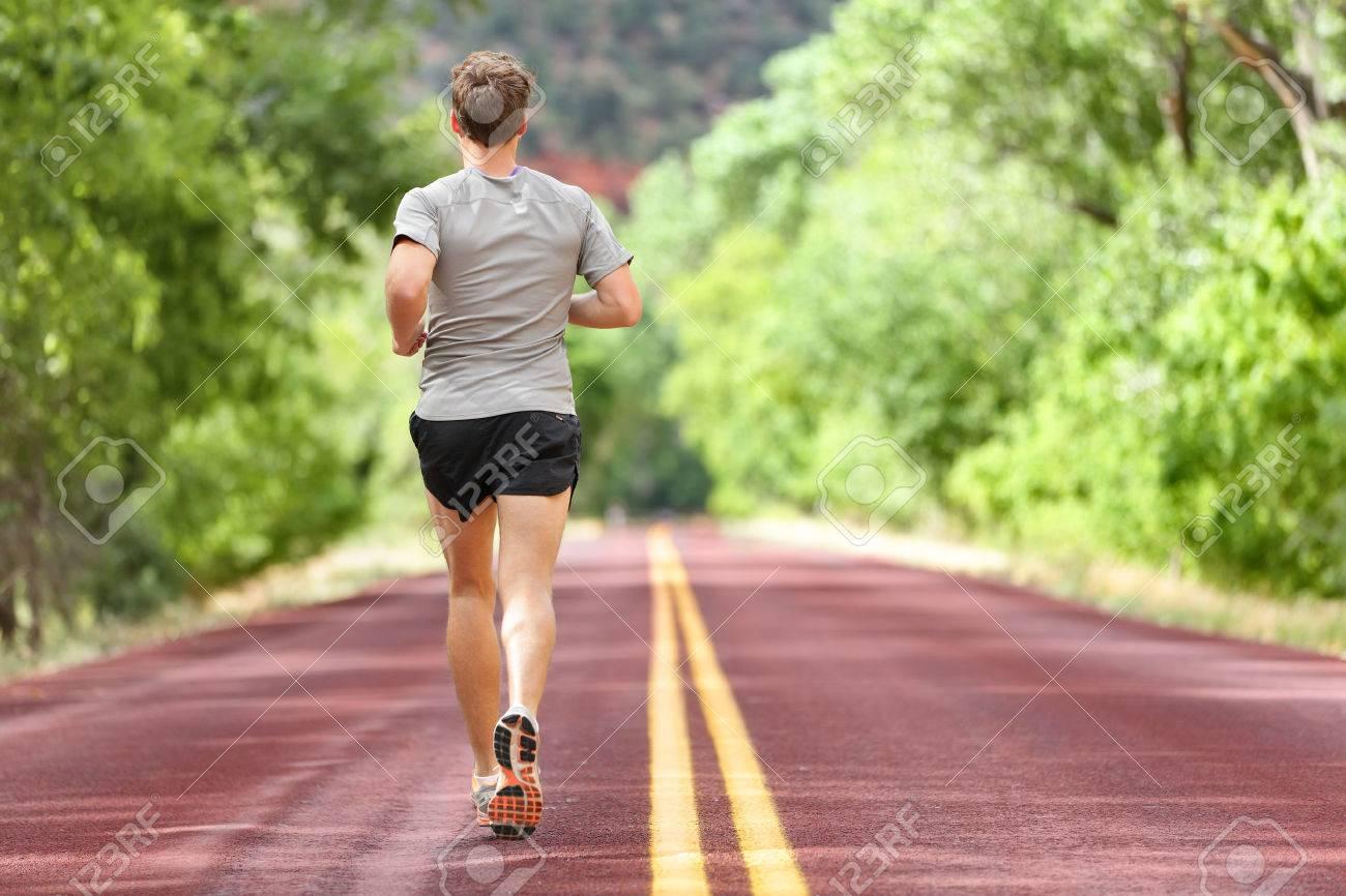Männlich running on road Training für die Fitness. Man tut Joggen Training im Sommer im Freien in der Natur laufen. Athlete in Laufschuhe und Shorts