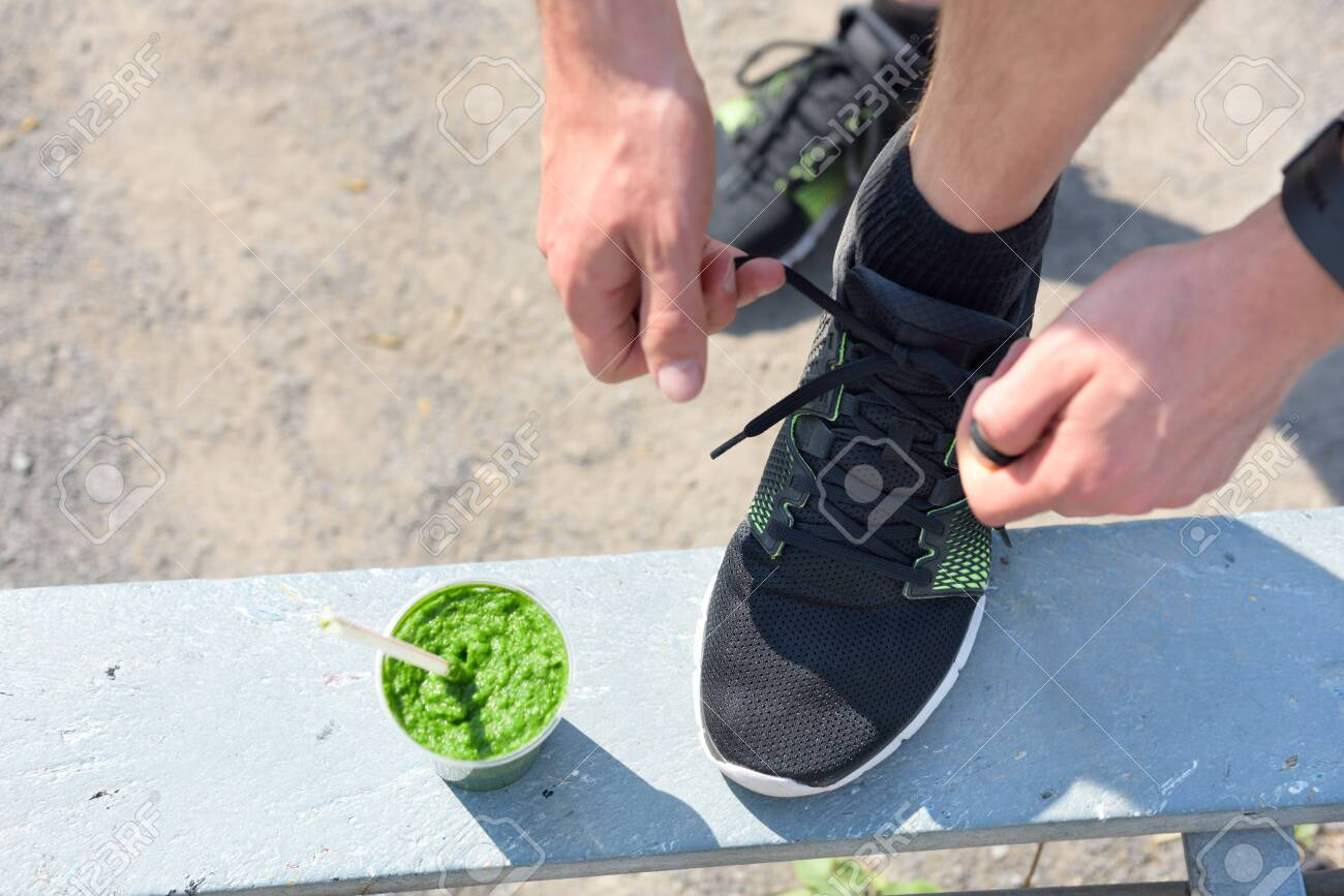 Green smoothie and running - healthy lifestyle. Closeup of male runner's sport shoe tying laces on park bench for diet and weight loss concept for men. Getting ready for jogging and cardio workout. - 121643978