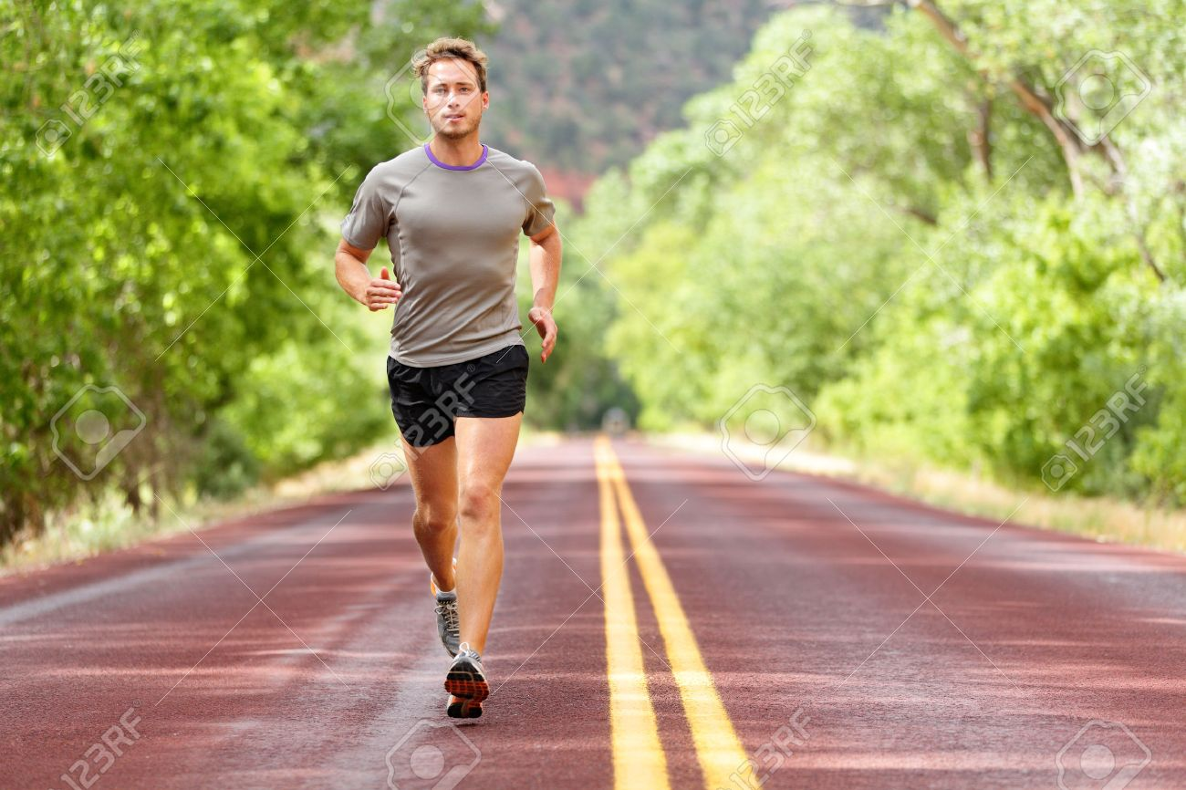 Sport and fitness runner man running on road training for marathon run doing high intensity interval training sprint workout outdoors in summer. - 44400128