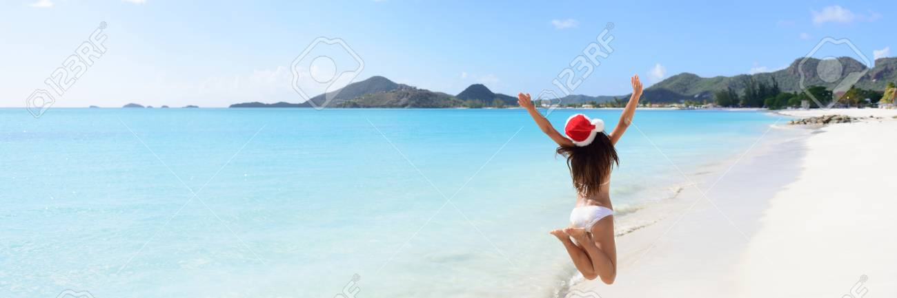 138251d6d87 Stock Photo - Woman with arms outstretched jumping at beach. Rear view of  female is wearing Santa hat and bikini. Carefree tourist is enjoying  Christmas ...