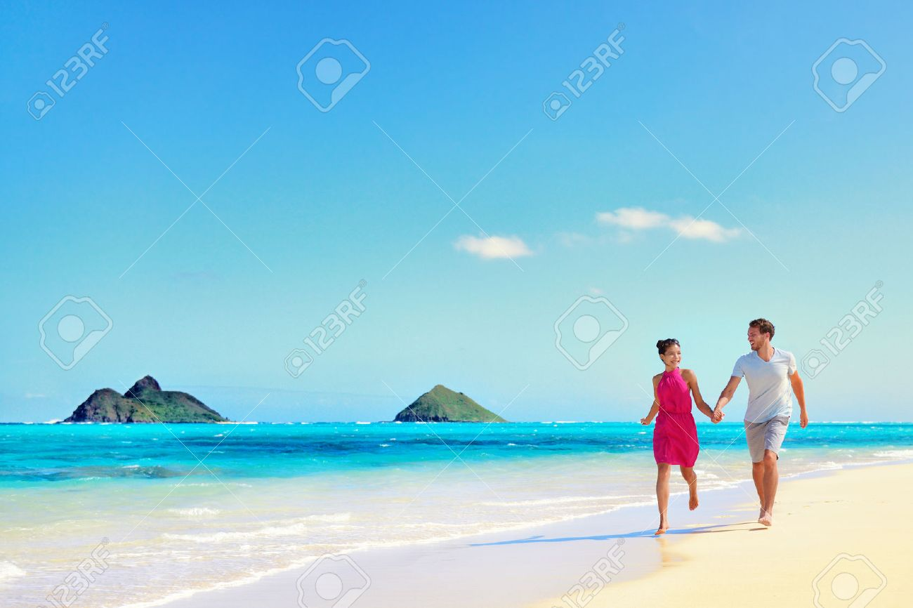 Hawaii vacation couple walking relaxing on white sand and pristine turquoise ocean water on Hawaiian beach Lanikai, Oahu island, USA. Holiday background with blue sky copy-space for travel concept. Stock Photo - 53758642