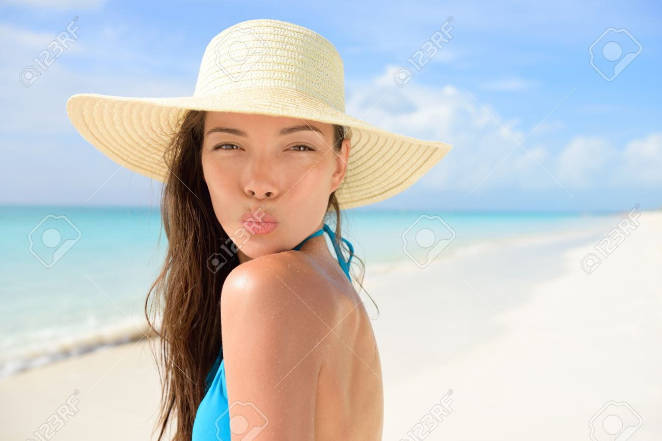 Beach sun hat woman blowing cute kiss on vacation. Asian female young adult  model striking eb178dd0f49