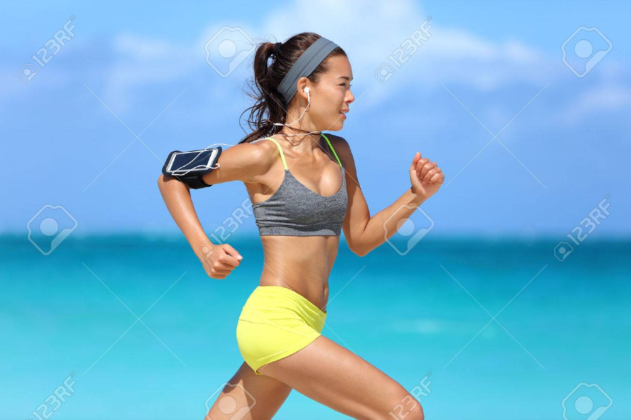 Athlete running woman runner listening to music on her phone sports armband with touchscreen and headphones earphones on summer beach. Fitness girl jogging fast training cardio and glutes. - 53759179