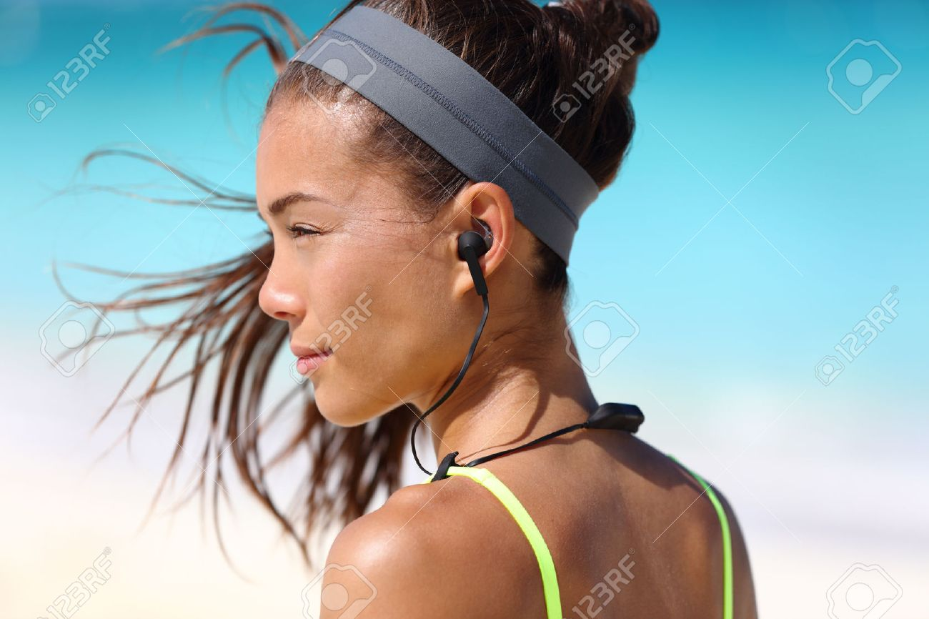 2de1a585834 Fitness girl with sport in-ear wireless headphones. Asian female athlete  woman runner wearing