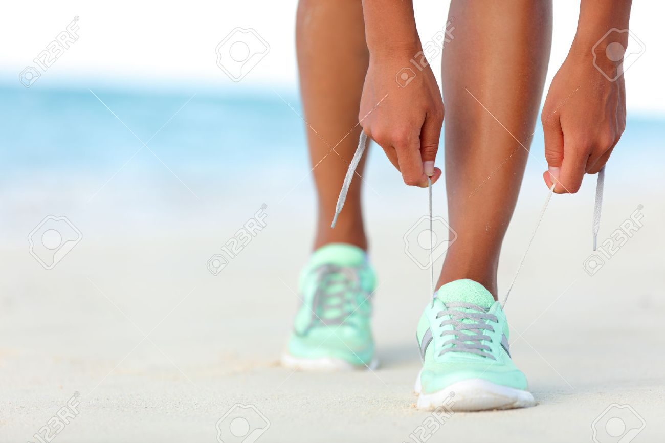 Runner woman tying laces of running shoes preparing for beach jogging. Closeup of hands lacing cross training sneakers trainers for cardio workout. Female athlete living a fit and active life. - 53759567