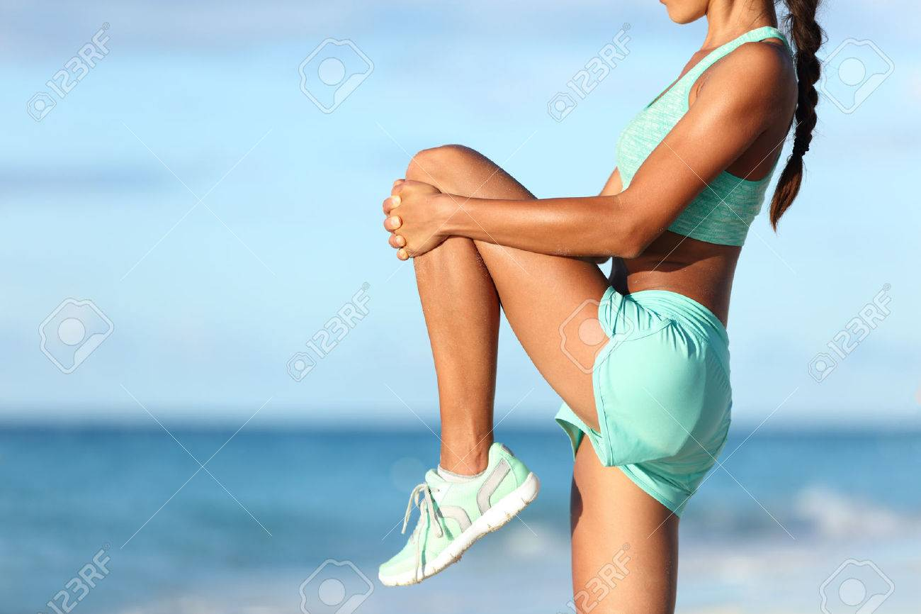 Fitness runner body closeup doing warm-up routine on beach before running, stretching leg muscles with standing single knee to chest stretch. Female athlete preparing legs for cardio workout. - 53759665