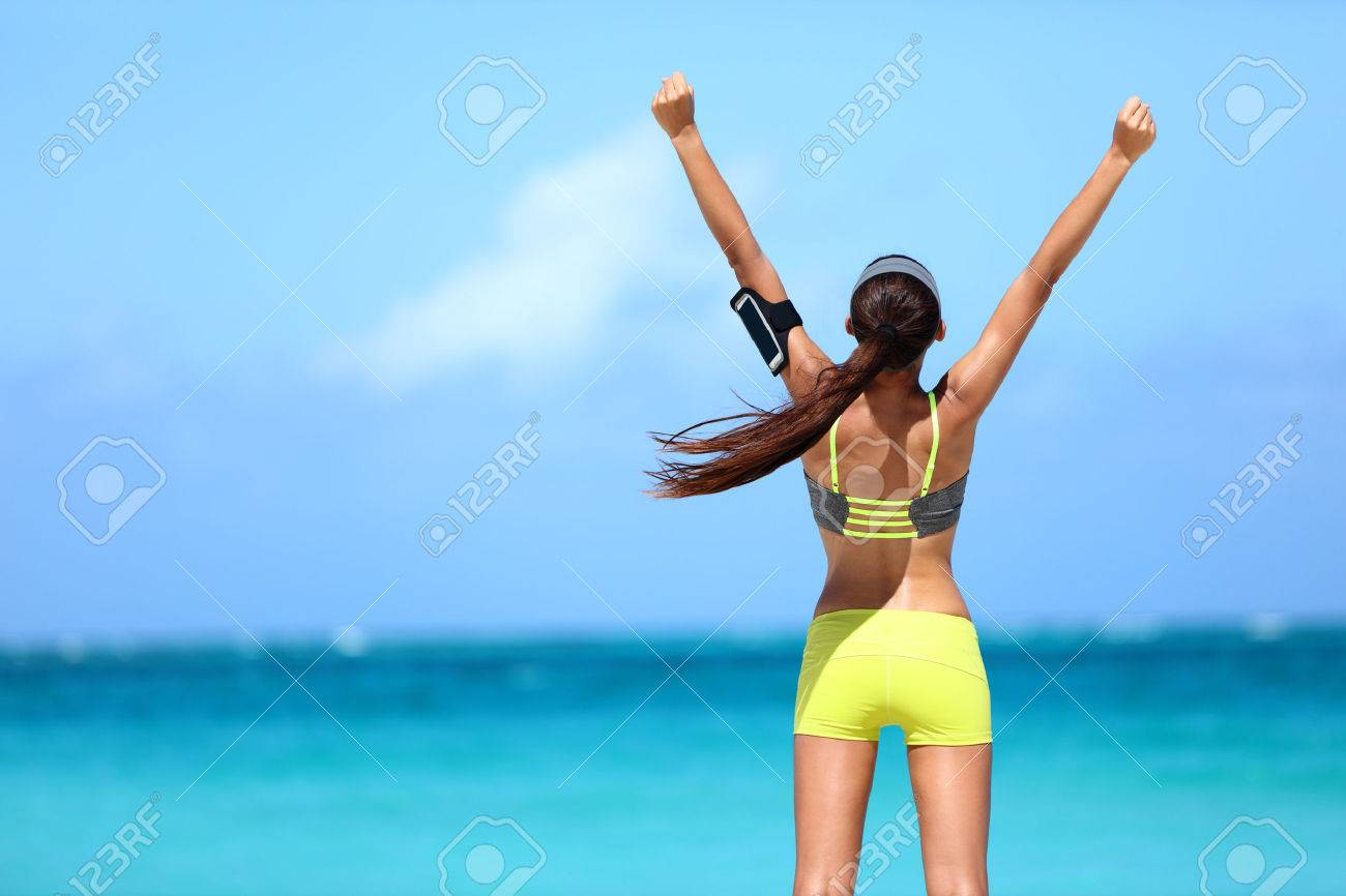 Strong fitness athlete arms up in success on summer beach after cardio training workout. Female runner woman running winning reaching goal achievement during strength training showing power. - 53759777