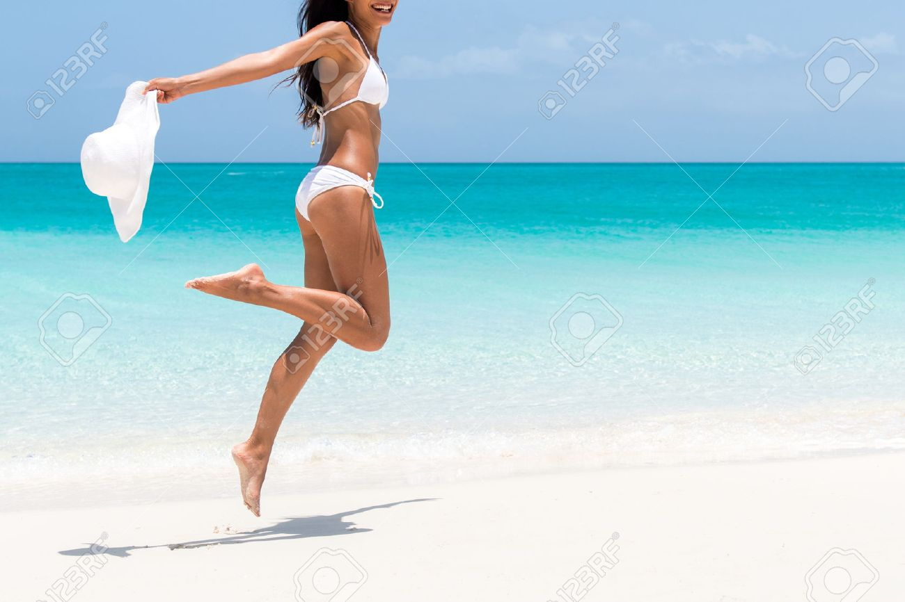 Beach ready bikini body - sexy slim legs and toned thighs and butt. Suntan happy woman jumping in freedom on white sand with sun hat. Weight loss success or epilation concept. Stock Photo - 54263731