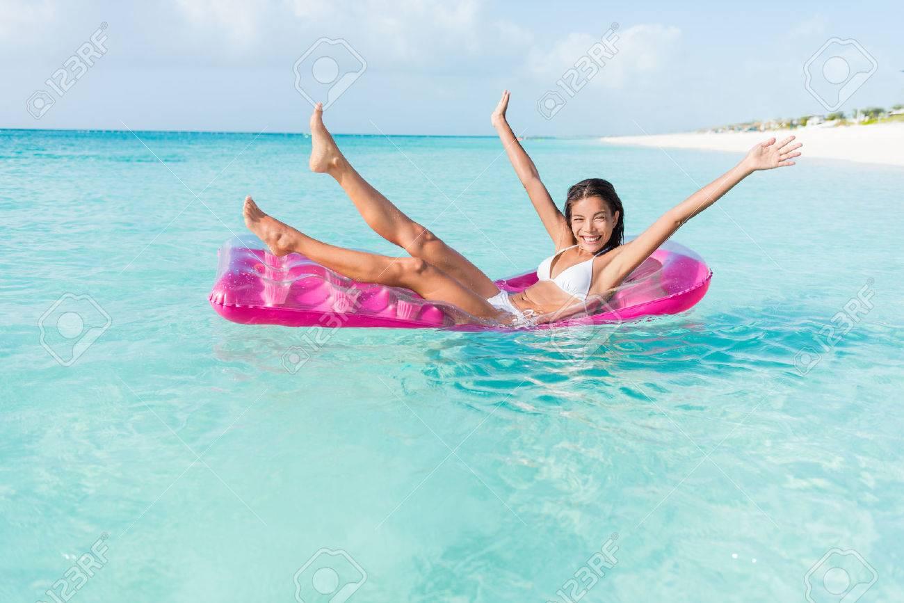 Plage fille fun ludique sur matelas piscine flottante rose flottant sur les vacances d'eau de l'océan escapade. femme Party applaudir jambes et les bras sur gonflable piscine de lit de jouet dans la mer turquoise. Banque d'images - 54263733