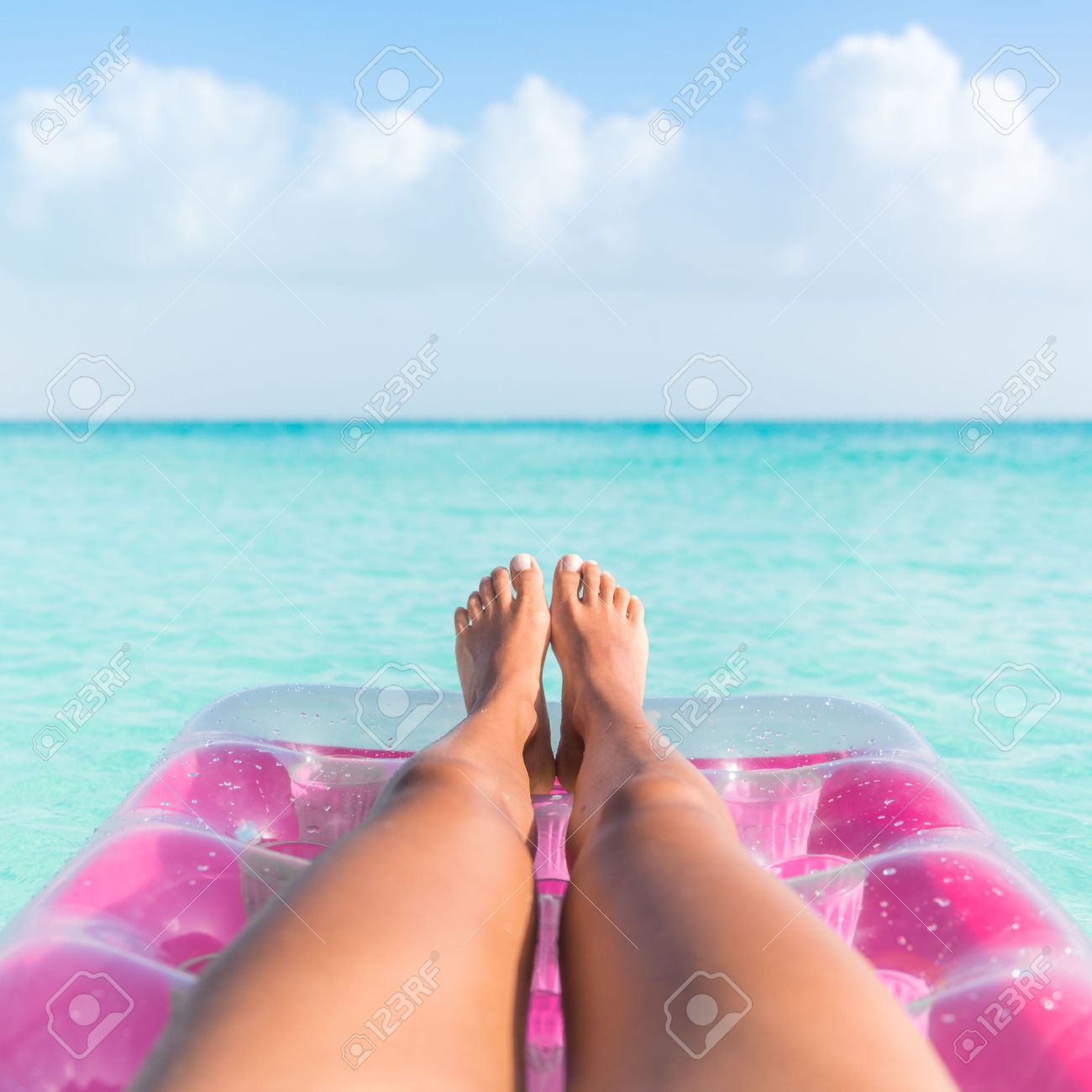 Summer vacation girl lower body closeup. Woman tanning legs  relaxing in ocean on pink inflatable swimming pool air mattress bed floating in turquoise water background. Suntan at tropical beach. Banque d'images - 54264152
