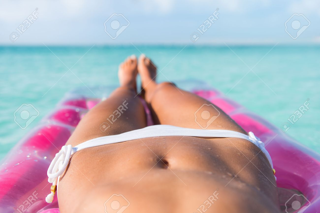 Sexy corps bikini gros plan abs estomac et jambes bronzées de plage femme bronzage sur matelas d'air lit sur l'océan turquoise ou la piscine de détente à une destination tropicale des Caraïbes. Banque d'images - 54264154