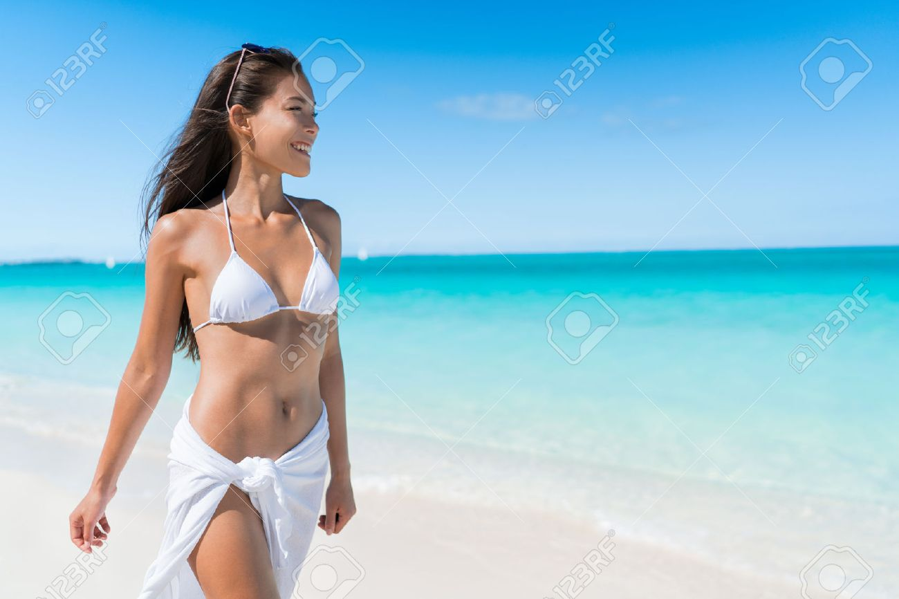 Bikini woman relaxing in white sun protection beachwear walking on tropical Caribbean beach with turquoise ocean water during summer vacations. Happy lifestyle Asian girl. Stock Photo - 54264158