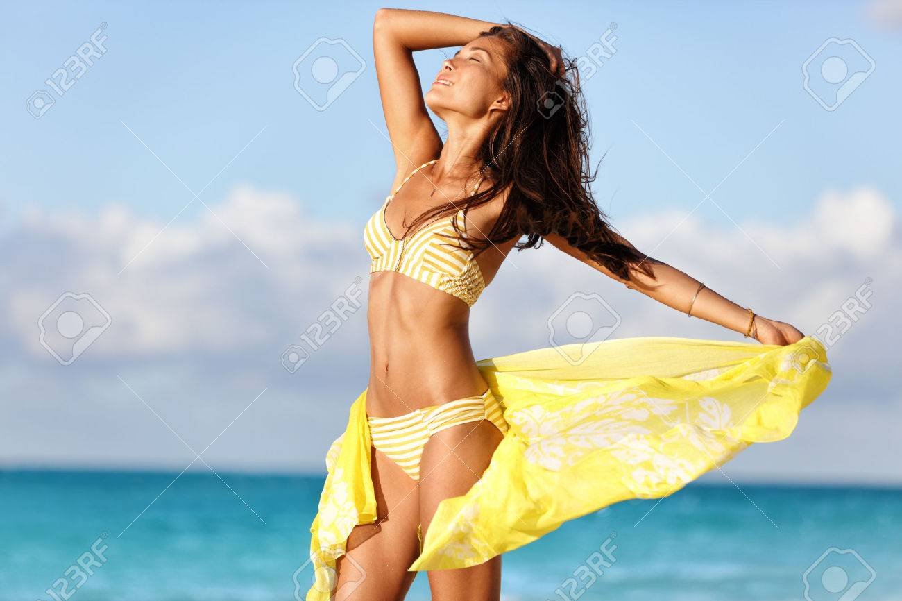 Sexy suntan woman relaxing enjoying sunset on beach with beachwear cover-up wrap showing slim bikini body for weight loss and skin care epilation concept. Asian model sunbathing during summer holiday. Stock Photo - 54454565