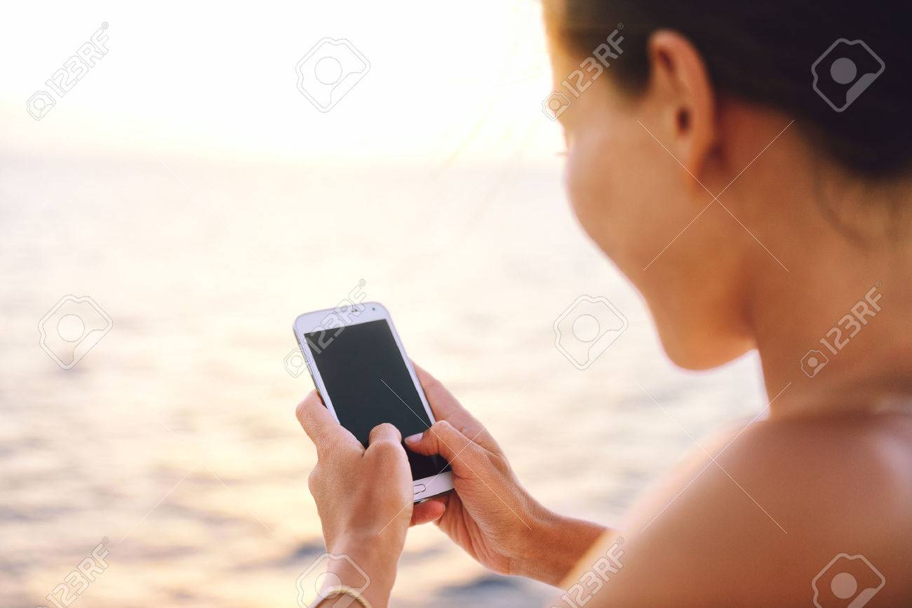 Smartphone woman texting on social media app looking at display screen for sms reading on ocean background on a sea cruise balcony or beach at sunset on holiday. Unrecognizable girl using smart phone. Stock Photo - 54454572
